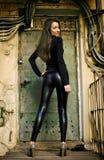 Jong vrouwelijk model dat zich vóór deur bevindt Royalty-vrije Stock Foto