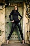 Jong vrouwelijk model dat zich vóór roestige deur bevindt Stock Afbeeldingen