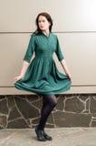 Jong vrouwelijk model die haar groene kleding opheffen Stock Foto