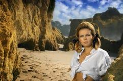 Jong vrouwelijk model op rotsachtig strand Stock Fotografie