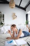 Jong vrouwelijk schilder het schilderen beeld op vloer thuis stock afbeelding