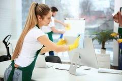 Jong vrouwelijke werknemer schoonmakend bureau royalty-vrije stock afbeelding