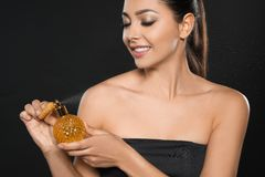 Jong vrouwen bespuitend parfum op zwarte royalty-vrije stock foto's
