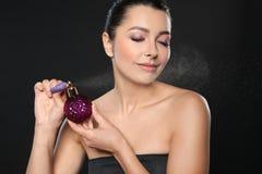 Jong vrouwen bespuitend parfum op zwarte royalty-vrije stock afbeeldingen