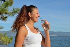 Jong vrouwen drinkwater na het uitoefenen Royalty-vrije Stock Afbeeldingen