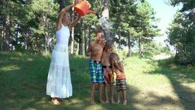 Jong vrouwen gietend water van een gieter op gelukkige jongens stock video