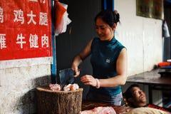 jong vrouwen hakkend vlees bij de lokale straatmarkt terwijl haar echtgenootslaap bij de achtergrond stock foto's
