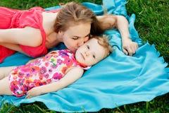Jong vrouwen kussend meisje die op blauwe deken liggen Stock Fotografie