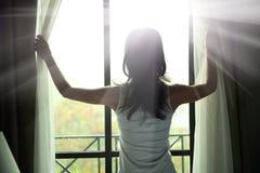 Jong vrouwen open venster Stock Afbeeldingen