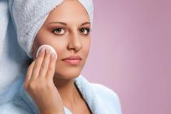 Jong vrouwen schoonmakend gezicht met katoenen stootkussen stock afbeelding