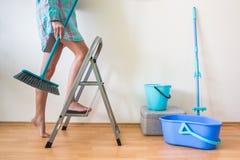 Jong vrouwen schoonmakend huis met ladder en borstel stock fotografie