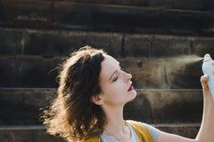 Jong vrouwen verfrissend gezicht met thermisch water Het genieten van, huidzorg, hitteconcept Royalty-vrije Stock Afbeelding
