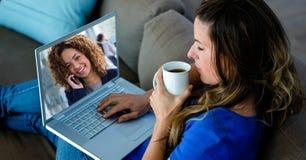 Jong vrouwen videoconfereren op laptop terwijl het hebben van koffie stock foto