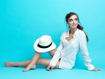 Jong vrouwen wit overhemd, hoed, blauwe achtergrond Stock Foto