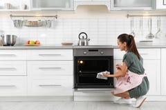 Jong vrouwenbaksel iets in oven stock afbeelding
