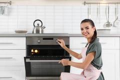 Jong vrouwenbaksel iets in oven royalty-vrije stock fotografie
