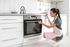 Jong vrouwenbaksel iets in oven stock foto's