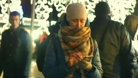 Jong vrouwengebruik van mobiele telefoon bij Kerstmismarkt stock video