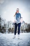 Jong vrouwenijs die in openlucht op een vijver schaatsen stock foto's