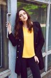 Jong vrouwenportret in zwarte trenchcoat en gele blouse Stock Fotografie