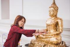 Jong vrouwenreiziger gezet bladgoud op het standbeeld van Boedha in de tempel van Thailand Royalty-vrije Stock Fotografie