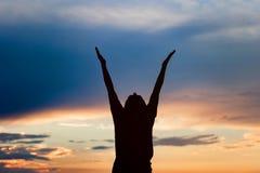 Jong vrouwensilhouet bij zonsondergang stock foto's