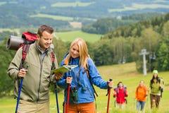 De jonge wandelende vrienden die kaart lezen vinden spoor Royalty-vrije Stock Afbeeldingen