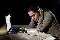 Jong wanhopig universitair studentenmeisje die in spanning voor examen met boeken en computerlaptop laat bij nacht bestuderen Stock Fotografie