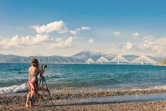 Jong wijfje in de kleding op het strand met driepoot en camera die beeld van brug rion-Antirion nemen dichtbij Patras, Griekenlan Stock Foto