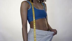 Jong wijfje die de resultaten van het gewichtsverlies tonen, standhoudend appel, gewichtscontrole stock video