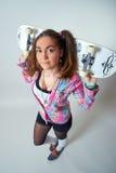 Jong wijfje die een skateboard houden stock afbeeldingen