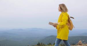 Jong wijfje die im gele regenjas met een rugzak in bergen wandelen die document kaart in handen houden stock videobeelden