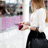 Jong wijfje die in modieuze kleren een portefeuille in sho onderzoeken Stock Fotografie