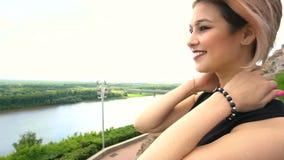 Jong wijfje die neer op een rivier vanaf de bovenkant van stad kijken stock videobeelden