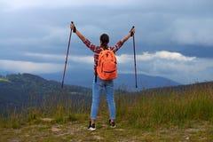 Jong wijfje met de uitgestrekte handen van wandelingspolen stock afbeelding