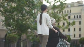 Jong wijfje op gang met gehandicapt bejaard mannetje in rolstoel, familiesteun stock videobeelden