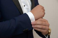 Jong wit Kaukasisch mannetje in avondkleding, die zijn manchetknopenteken van sprezzatura en elegantie bevestigen stock afbeelding