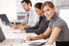 Jong zakenlui die bij vergaderingslijst zitten stock foto's