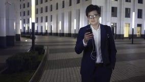 Jong zakenmanweb die terwijl het lopen in een nachtstad surfen stock video