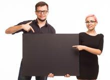 Jong zeker paar die presentatie tonen die aanplakbiljet richten Stock Afbeelding
