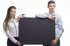 Jong zeker paar die presentatie tonen die op aanplakbiljet richten Stock Afbeeldingen