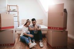 Jong zich in nieuw huis bewegen en paar die selfie nemen royalty-vrije stock foto