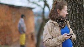 Jong zwanger meisje in beige uitstekende retro laag die haar smartphone, geheimzinnige mens in gele broeken gebruiken die zich in stock video