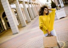 Jong zwarte met krullend haar in het winkelen stock foto