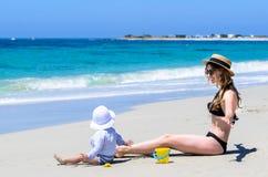 Jonge aanbiddelijke moeder die pret met weinig dochter hebben bij tropisch strand royalty-vrije stock fotografie