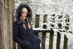 Jonge aanbiddelijke vrouw die het blauwe laag genieten dragen die met een kap in de winterbos in openlucht wandelen De versheidsc Royalty-vrije Stock Fotografie