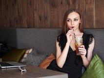 Jonge aanbiddelijke vrouw die met schitterende ogen in make-up en modieuze uitrusting grote glaskop van koffie met stro drinken d stock fotografie