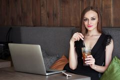 Jonge aanbiddelijke vrouw die met schitterende ogen in make-up en modieuze uitrusting grote glaskop van koffie met stro drinken d stock foto's