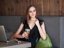 Jonge aanbiddelijke vrouw die met schitterende ogen in make-up en modieuze uitrusting grote glaskop van koffie met stro drinken d stock afbeelding