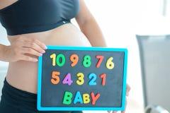 Jonge aanstaande moeder die met brievenblokken baby op haar zwangere buik spellen stock afbeelding